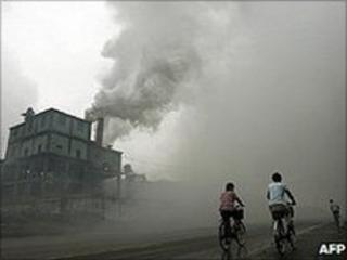 People cycling past a factory (Image: AFP)