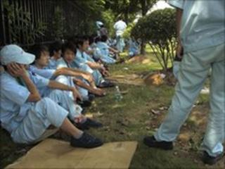 Workers rest during a strike at Denso in Guangdong province