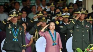 Philippine President Gloria Arroyo (C) salutes with outgoing Armed Forces chief of staff General Delfin Bangit (L) and acting chief of staff Lieutenant General Nestor Ochoa (R) during the testimonial parade for Bangit at the military headquarters in Manila on 22 June 2010.