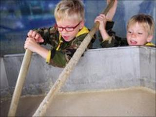 Boys stirring bowl of porridge