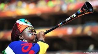 A South African fan blows a vuvuzela
