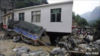 Damaged vehicles and buildings in Xiaohe, Yunnan, on 14 July 2010