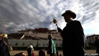 Pilgrims prostrate themselves in front of the Potala palace in Lhasa