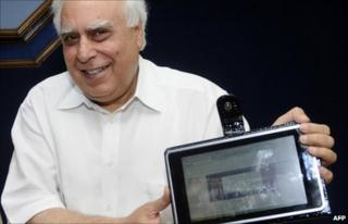 """Indian Minister for Human Resource Development Kapil Sibal unveils the """"laptop"""" device in Delhi on 22 July 2010"""