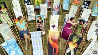 """People relax in London""""s Hyde Park with some of the deckchairs created by leading UK designers and a group of artists from Shanghai for Deckchair Dreams 2010"""