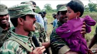 Tamil Tiger soldiers hold a child. File photo