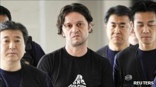Suspect Rifat Hadziahmetovic (centre) is escorted by Japanese authorities upon his arrival for trial at Narita international airport, east of Tokyo