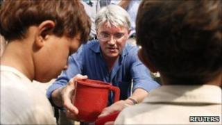 Andrew Mitchell and two flood survivors in Nowshera in Pakistan on 18 August