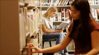Two girls in a library looking at books