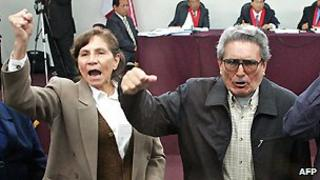 Shining Path leaders Elena Iparraguirre and Abimael Guzman raise their fists after their trial was deferred on 5 November 2004.