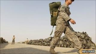 A US soldier from the 1st Battalion, 116th Infantry Regiment, carries his bag as he prepares to pull out from Iraq to Kuwait, at Tall Air Base near Nasiriya, on 15 August 2010.