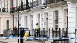 A PCSO stands outside a building where the body of an unnamed man was discovered in a top floor apartment