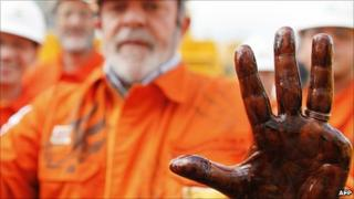 Picture released by the Brazilian Presidency showing Brazilian President Luiz Inacio Lula da Silva with his hand dirty with pre-salt oil on 15 July 2010.