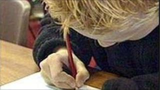 Boy writing in classroom