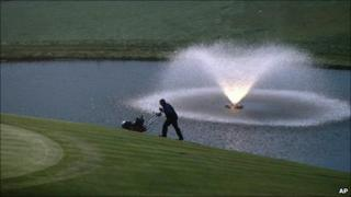 A greenkeeper prepares the 18th green for the 2010 Ryder Cup golf tournament in Newport