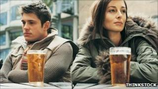 Two people drinking pints