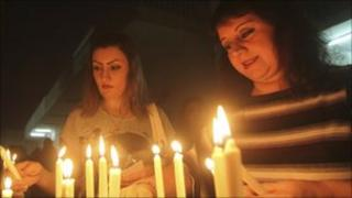 Catholics light candles at a church in Baghdad. Photo: October 2010