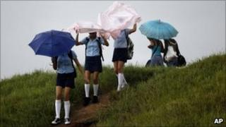 Students in Pinar del Rio cover themselves from the rain