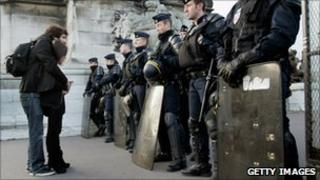 People stand in front of police during a protest in Paris, 19 October 2010