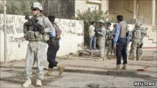 US soldiers and Iraqi policemen at the site of a bomb attack in Kirkuk, 250km (155 miles) north of Baghdad - 27 September 2010