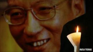 A protester holds a candle next to a portrait of Liu Xiaobo