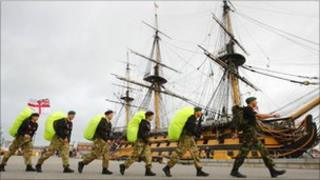 The Royal Navy team walking past HMS Victory
