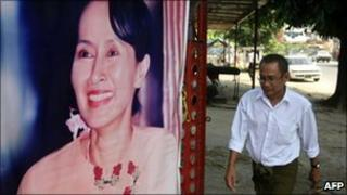 An NLD member walks past a picture of Aung San Suu Kyi as he arrives at the NLD headquarters in Rangoon