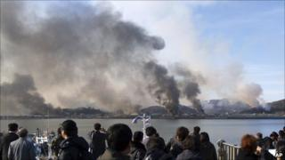 South Koreans watch smoke rising from Yeonpyeong island on 23 November 2010