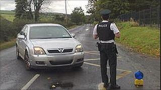 PSNI officer in front of car