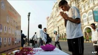 A man pays homage to those who died in the Mumbai attacks at a memorial outside the Taj hotel on 26 November 2010