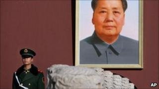 Soldier stands in front of a portrait of Mao Zedong in Tiananmen Square in Beijing