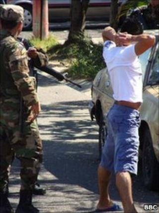 Police officer detains suspected gang member in San Salvador (December 2010)