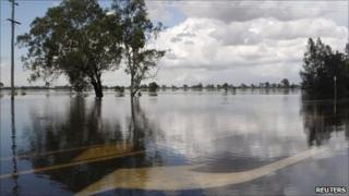 Water flows over road markings on a highway near Rockhampton on 3 Jan 2010