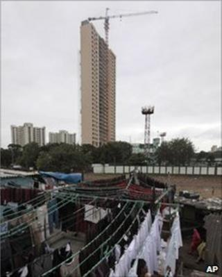 In this Nov. 9, 2010 file photo, an Indian laundry worker hangs clothes to dry on his terrace with the backdrop of the 31-story Adarsh Housing Society apartments in Mumbai, India.