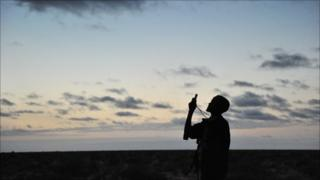 A militiaman looks into his mobile phone as he searches for a network signal in the early morning hours while travelling through the plains of central Somalia on 21 August 2010