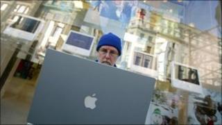 Man on a laptop outside a shop