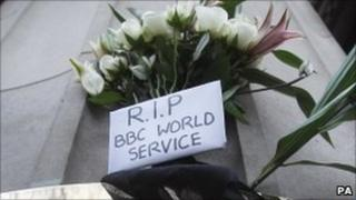 Protesters leave sign saying 'RIP World Service' outside BBC building