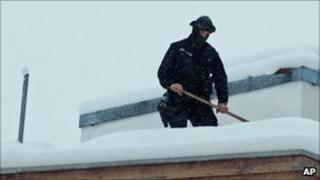 A security officer shovels snow off of a rooftop at the world economic forum in Davos, 26 January
