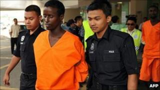 Malaysian police escort a suspected Somali pirate on 31 Jan 2011
