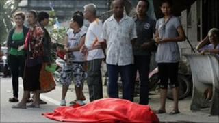 People stand next to the body of one of the victims of the shooting in Pattani on 3 Feb 2011