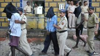 Indian police escort alleged pirates at a police station in Mumbai on 31 January 2011 after their arrest following a gun battle off the coast of Lakshadweep Islands