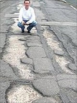 Cedar Way on Bellfields, Guildford, with potholes during an election campaign last year