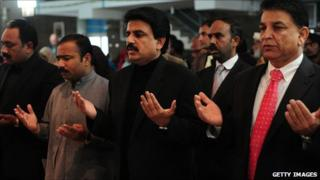 Pakistani Minister for Minorities Shahbaz Bhatti (C) and others pray for late Punjab Governor Salman Taseer at the Fatima Church in Islamabad 9 January 2011