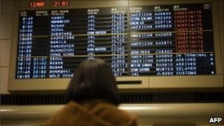 Woman looks at board at Narita airport