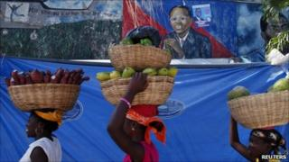 Women walk past a mural of former president Jean-Betrand Aristide in Port-au-Prince