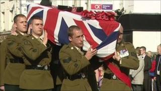 Coffin drapped in the Union flag carried by soldiers