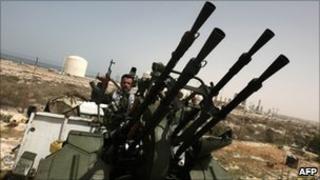 A Libyan rebel guards oil facilities near the rebel-held port town of Brega (29 March 2011)