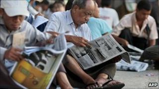 Burmese men reading newspapers