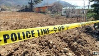 An excavated garlic field is seen behind a police line after police found buried cash, in the southwestern city of Gimje