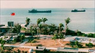 File photo shows two Taiwanese warships docking near Taiping Island, one of the disputed Spratly Island chain, with the Taiping military base in the foreground
